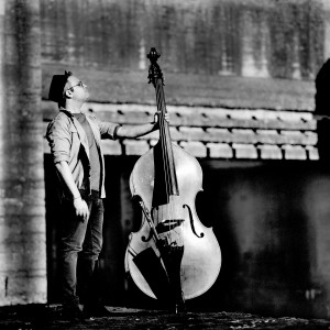 Adam Ben Ezra standing looking up holding his double bass.