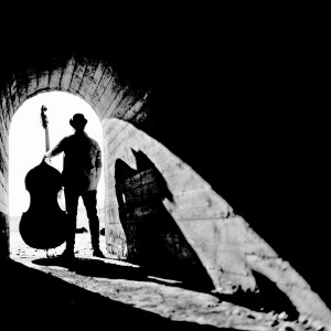 Adam Ben Ezra holding his double bass standing back at the end of a tunnel with his shadow.