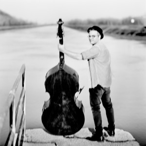 Adam Ben Ezra with his double bass standing at a river looking to the photo camera.