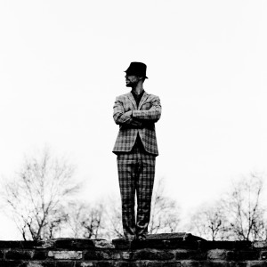 Charlie Winston standing on old brick wall with trees in the background wearing suit and a hat.