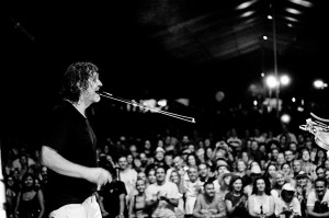 Emir Kusturica singing to the microphone on the stage at the concert of No Smoking Orchestra.