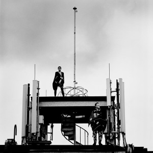 Gus Gus members Daniel Agust Haraldsson and Birgir Porarinsson standing on a broadcaster at the rooftop of the building with skies in the background.