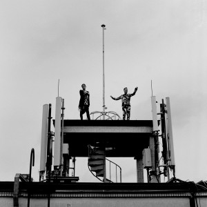 Gus Gus members Daniel Agust Haraldsson and Birgir Porarinsson posing on a broadcaster at the rooftop of the building with skies in the background.
