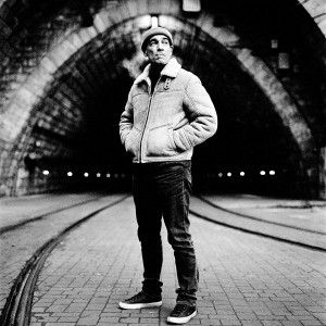 Jean-Marc Barr standing in front of a tunnel smoking cigarette and wearing a jacket.