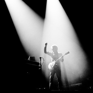 Jean-Michel Jarre playing guitar on the stage at his concert with one hand up.