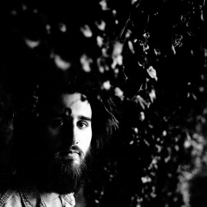 Face of Jean Rondeau under the tree in the darkness.