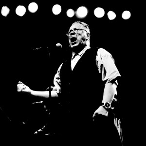 John Lyndon Pil singing to the microphone on the stage at a concert.