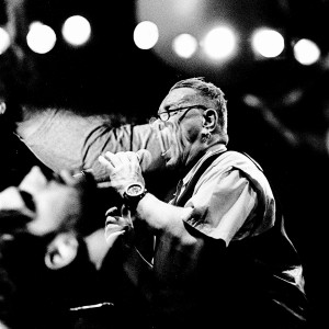 Double exposure of John Lydon Pil singing on the stage at his concert and people in the audience.