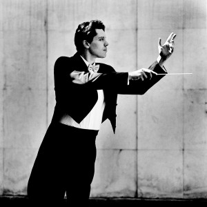 Kevin Griffiths making a conducting pose with a baton in his hand wearing a tuxedo.
