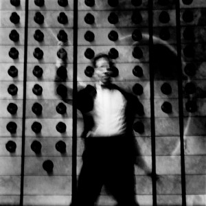 Fuzzy photograph of Kevin Griffiths conducting with the wall with black dots in the background.