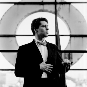 Kevin Griffiths holding baton in his hand wearing tuxedo in front of a giant letter O with a city view in the background.