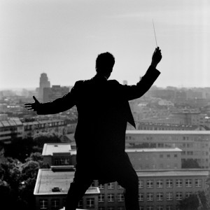 Kevin Griffiths posing from the back on the rooftop of a building with baton in his hand with a city view in the background.
