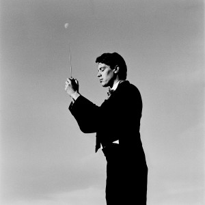 Kevin Griffiths standing holding baton in his hands with the skies in the background and the moon.