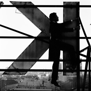 Kevin Griffiths climbing on a giant letter K at the rooftop of a building with city view in the background.