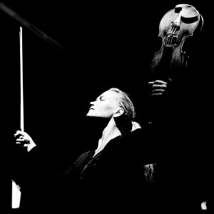 Mari Samuelsen making a gesture with her hands up holding a violin and a fiddlestick in the darkness.