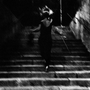 Mari Samuelsen walks the stairs holding violin and fiddlestick.