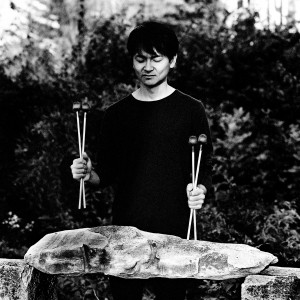 Masayoshi Fujita standing at his vibraphone holding the sticks in front of trees.