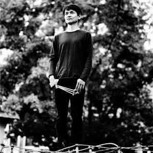Masayoshi Fujita standing holding the sticks in front of trees.