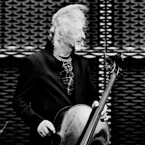 Misha Maisky posing with his cello with hair blown by wind looking to the right.