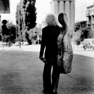 Misha Maisky from the back holding the cello case on the back.