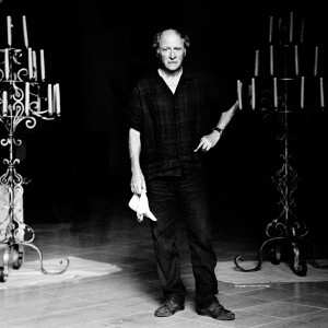 Robert Dornhelm standing and holding a handkerchief in his hand between two candlesticks.
