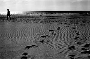 Theo Jansen walking on a beach with foot prints in the sand.
