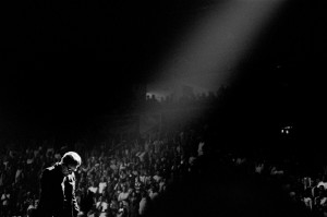 Bono Vox on the stage at a concert with audience with his head down.