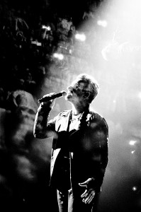 Double exposure of U2 frontman Bono Vox singing to the microphone with the audience.