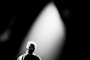 U2 frontman Bono Vox standing back on the stage in the light at the concert.